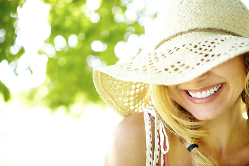 Smiling blonde with hat covering eyes with sun hat